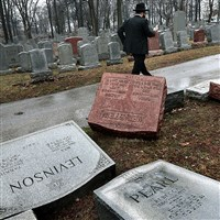 Rabbi Hershey Novack of the Chabad center walks through Chesed Shel Emeth Cemetery in University City on Tuesday, where almost 200 gravestones were vandalized over the weekend