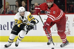 Penguins center Sidney Crosby and Carolina center Jordan Staal chase the puck during the second period Tuesday in Raleigh, N.C.