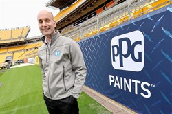 Bryan Iams, vice president of corporate, government and community affairs for PPG Industries stands along signage for his company Tuesday at Heinz Field.
