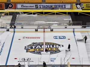 Crews uncover ice Tuesday at Heinz Field in preparation for the Penguins' game against the Flyers on Saturday.