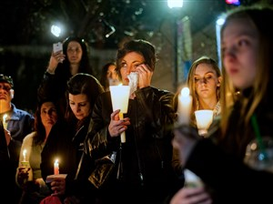 Nicole Keating, center, 44, of Elwood City, wipes a tear from her eyes Monday at Katz Plaza, Downtown. Ms. Keating and about 70 others held a candlelight vigil for missing North Side resident Dakota James, who was last seen cutting through the plaza on the night of Jan. 25th.