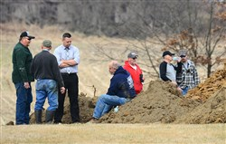 Family members and friends gather near the site where Adam Skokut Jr., 18, was killed Wednesday when a trench collapsed as he and his father worked to install a septic system at their home near South Huntingdon, Westmoreland County