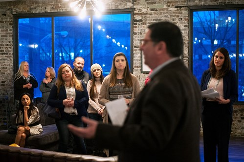 Immigrants and other guests listen to Mayor Bill Peduto on Tuesday in Braddock as he speaks at a news conference highlighting new data on the economic impact of immigrants. The event was held at Braddock Mayor John Fetterman's home.