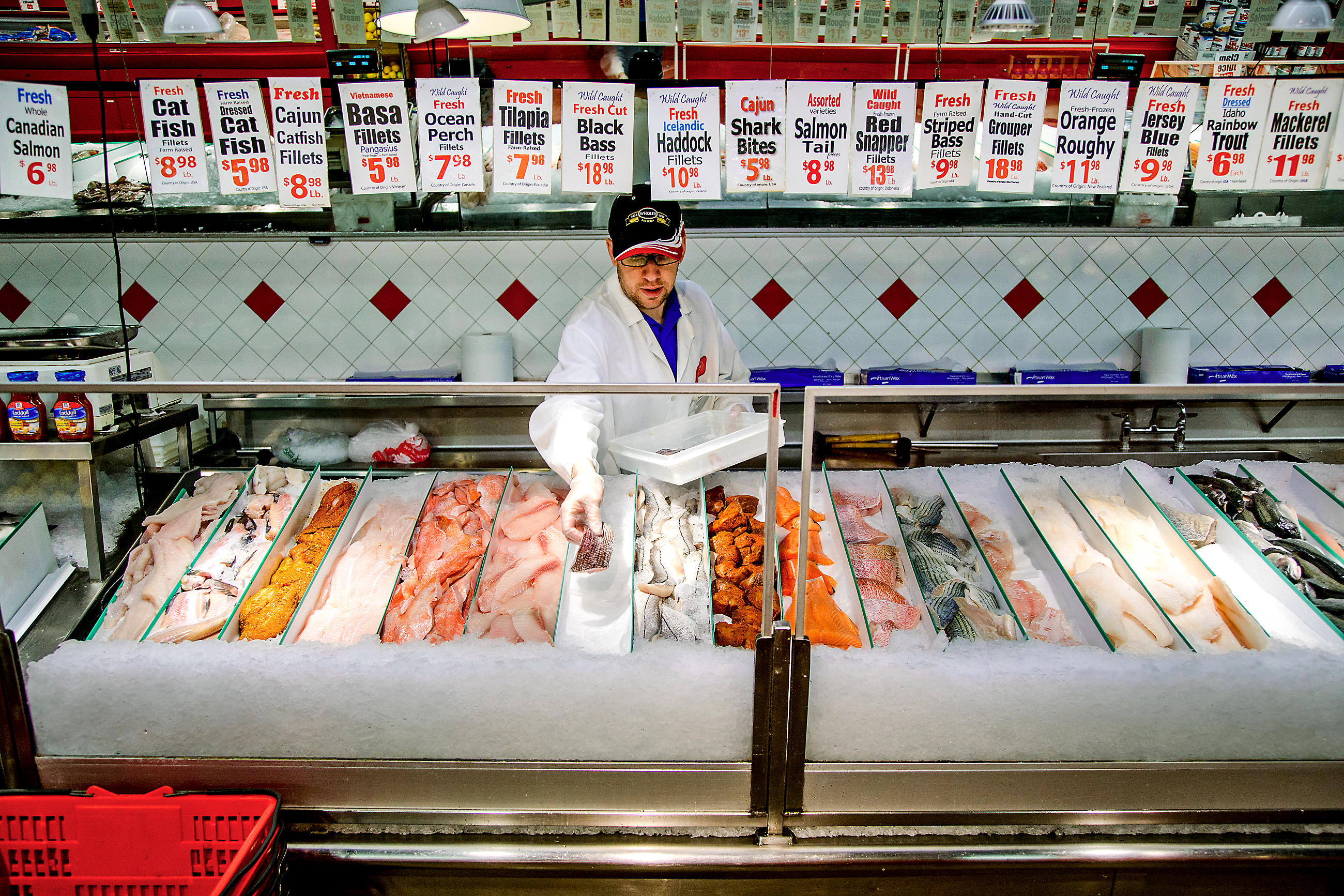 20170222arFishinStrip01 Jonathan Cunningham restocks the fillet counter at Wholey's fish market in the Strip District.