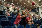 Fans reach to catch T-shirts thrown during a timeout as Duquesne faces Fordham Feb. 22 at the Palumbo Center.