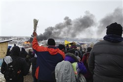 A fire burns in the background as opponents of the Dakota Access pipeline leave their main protest camp Wednesday, near Cannon Ball, N.D., as authorities were preparing to shut down the camp in advance of spring flooding season.