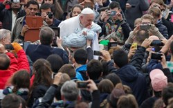 Pope Francis kisses a baby as he leads the weekly general audience in Saint Peter's Square at the Vatican Wednesday.