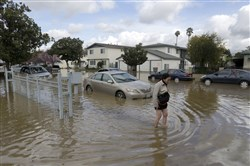 Hien Nguyen walks through flooded waters on Welch Avenue in San Jose, Calif. on Wednesday. Rising floodwaters sent thousands of residents fleeing inundated homes in San Jose and forced the shutdown of a major freeway Wednesday.