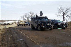 Law enforcement vehicles arrive at the closed Dakota Access pipeline protest camp near Cannon Ball, N.D., on Thursday.