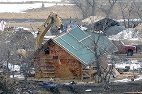 A backhoe rips through a wood structure to begin the cleaning up process at the Oceti Sakowin camp as law enforcement swept through the camp arresting the final Dakota Access oil pipeline protesters in Morton County Thursday, Feb. 23, 2017, near Cannon Ball, N.D.