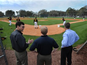 Pirates owner Bob Nutting, left, general manager Neal Huntington and president Frank Coonelly, right, huddle behind home plate to watch the workouts in 2010 at Pirate City in Bradenton, Fla.