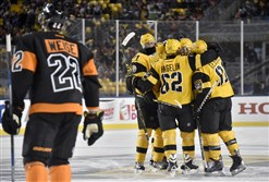 The Penguins gather to congratulate Chad Ruhwedel on a goal against the Philadelphia Flyers in the third period of the Stadium Series Saturday at Heinz Field.
