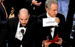 """La La Land"" producer Jordan Horowitz, left, shows the card reading Best Picture ""Moonlight"" during the Academy Awards ceremony Sunday night. Actor Warren Beatty is in the background."