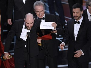 """Jordan Horowitz, producer of """"La La Land,"""" shows the envelope revealing """"Moonlight"""" as the true winner of best picture at the Oscars on Sunday. Presenter Warren Beatty and host Jimmy Kimmel look on."""