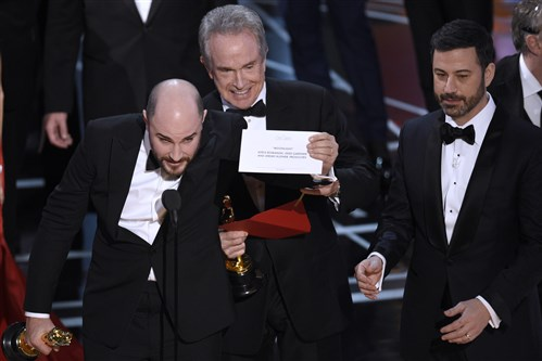 "Jordan Horowitz, producer of ""La La Land,"" shows the envelope revealing ""Moonlight"" as the true winner of best picture at the Oscars on Sunday. Presenter Warren Beatty and host Jimmy Kimmel look on."