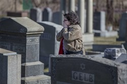 Stacy Silver is overcome with emotion as she searchers for loved ones' headstones at Mount Carmel Cemetery in Philadelphia.
