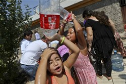 Two girls refresh themselves while residents gather water from a fire hydrant at a neighborhood in Santiago, Chile, on Monday.