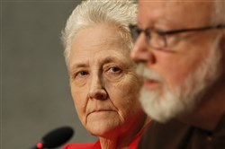 Marie Collins listens in 2014 as Cardinal Sean O'Malley, the archbishop of Boston, speaks during a press conference.
