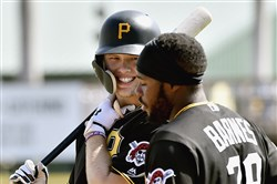 Pirates center fielder Austin Meadows talks with Barrett Barnes during batting practice before taking on the Yankees March 6 at LECOM Park in Bradenton, Fla.