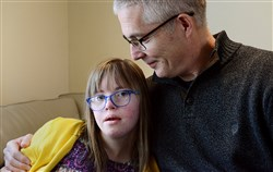 "Chloe Kondrich, then 13, with her father Kurt, in 2017, at their home in Upper St. Clair. ""Chloe's law,"" named after Chloe Kondrich, who was born with Down syndrome, was signed by Gov. Tom Corbett in 2014 and requires that health providers make information about early intervention services for Down syndrome kids available to expectant mothers who get the diagnosis."