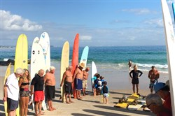 The assembled prepare to honor Ollie, a dearly departed fellow surfer.