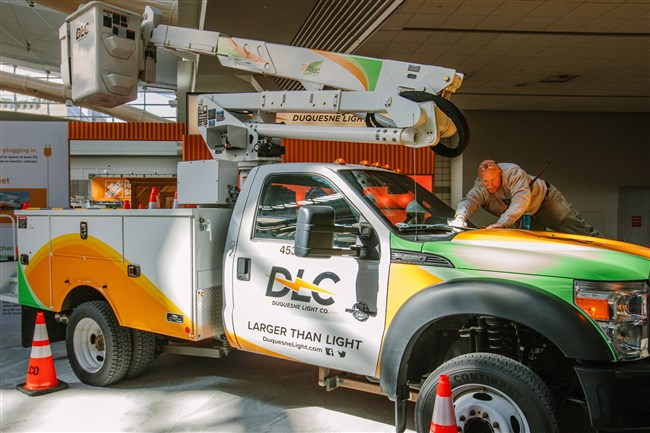 """John Freund, a carpenter with Carpenter Connection, cleans the window of an electric powered utility truck on display as a part of Duquesne Light's """"Electric Lane"""" display at the Home and Garden show at the convention center on Thursday."""