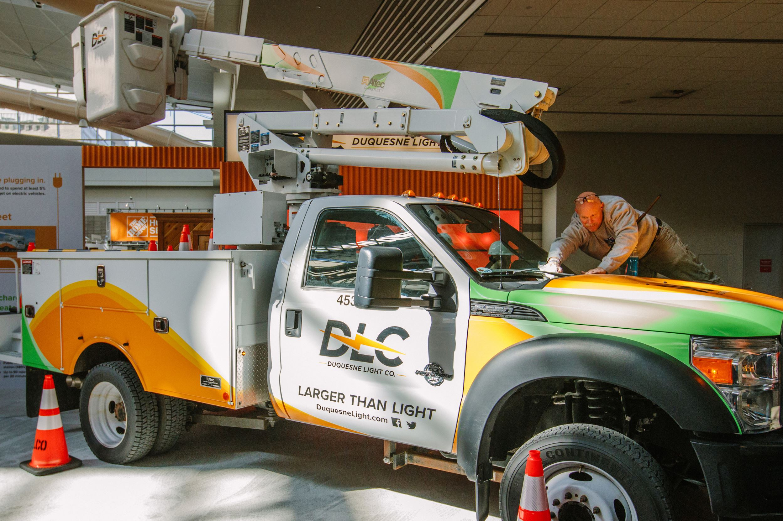 "20170309arElectricTrucks03-2 John Freund, a carpenter with Carpenter Connection, cleans the window of an electric powered utility truck on display as a part of Duquesne Light's ""Electric Lane"" display at the Home and Garden show at the convention center on Thursday."