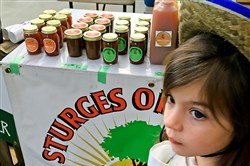 A young visitor to last year's Farm to Table Conference walks past a display table in the exhibitor hall.
