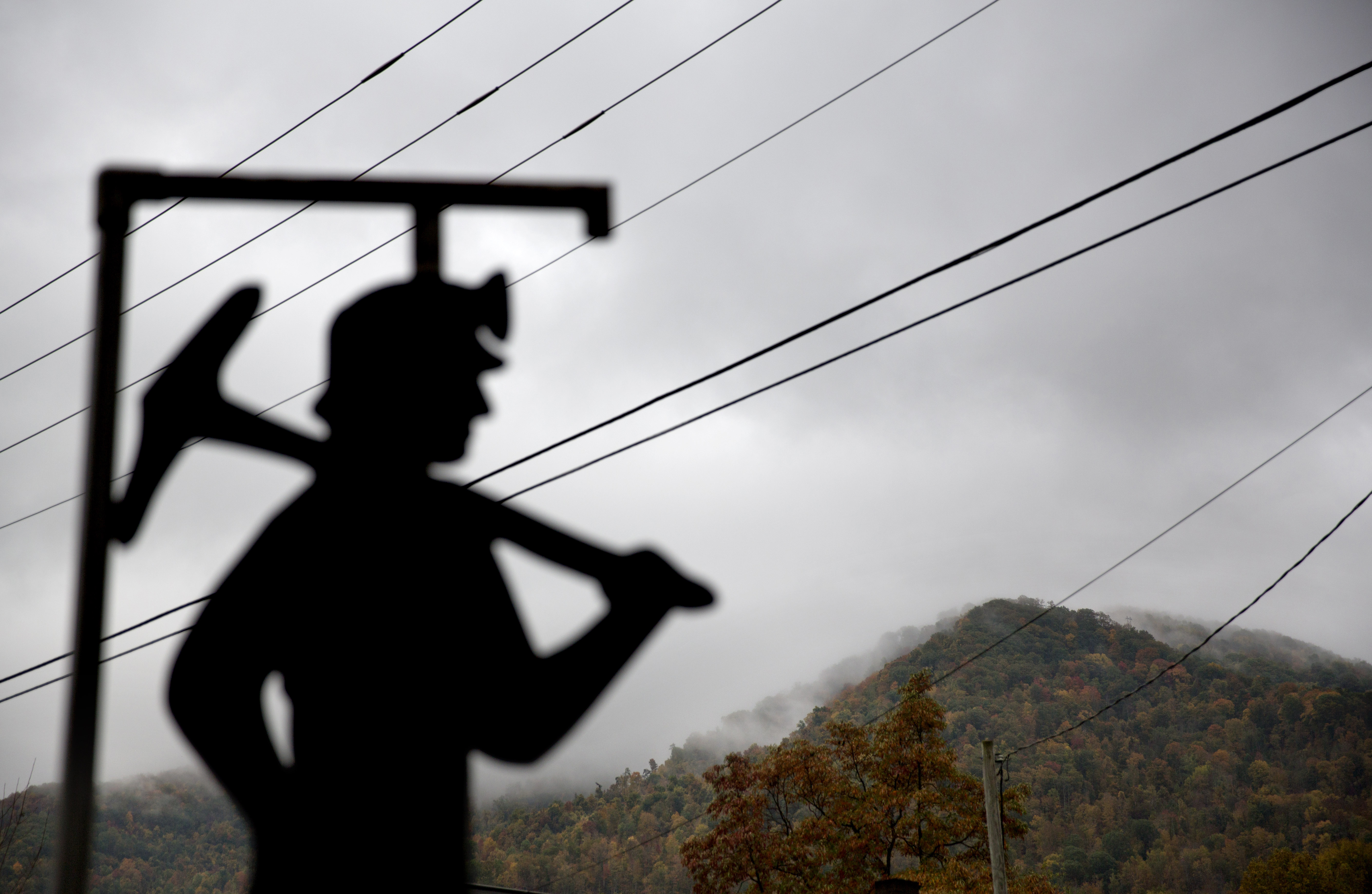 Nuclear Power Kentucky FILE - In this Oct. 16, 2014 file photo, fog hovers over a mountaintop as a cutout depicting a coal miner stands at a memorial to local miners killed on the job in Cumberland, Ky. The Republican-controlled Kentucky state legislature is on the cusp of lifting its decades-long moratorium on nuclear energy, a move unthinkable just three years ago in a state that has been culturally and economically dominated by coal. As the coal industry continues its slide, even Republican lawmakers are acknowledging a need for alternatives. (AP Photo/David Goldman, File)