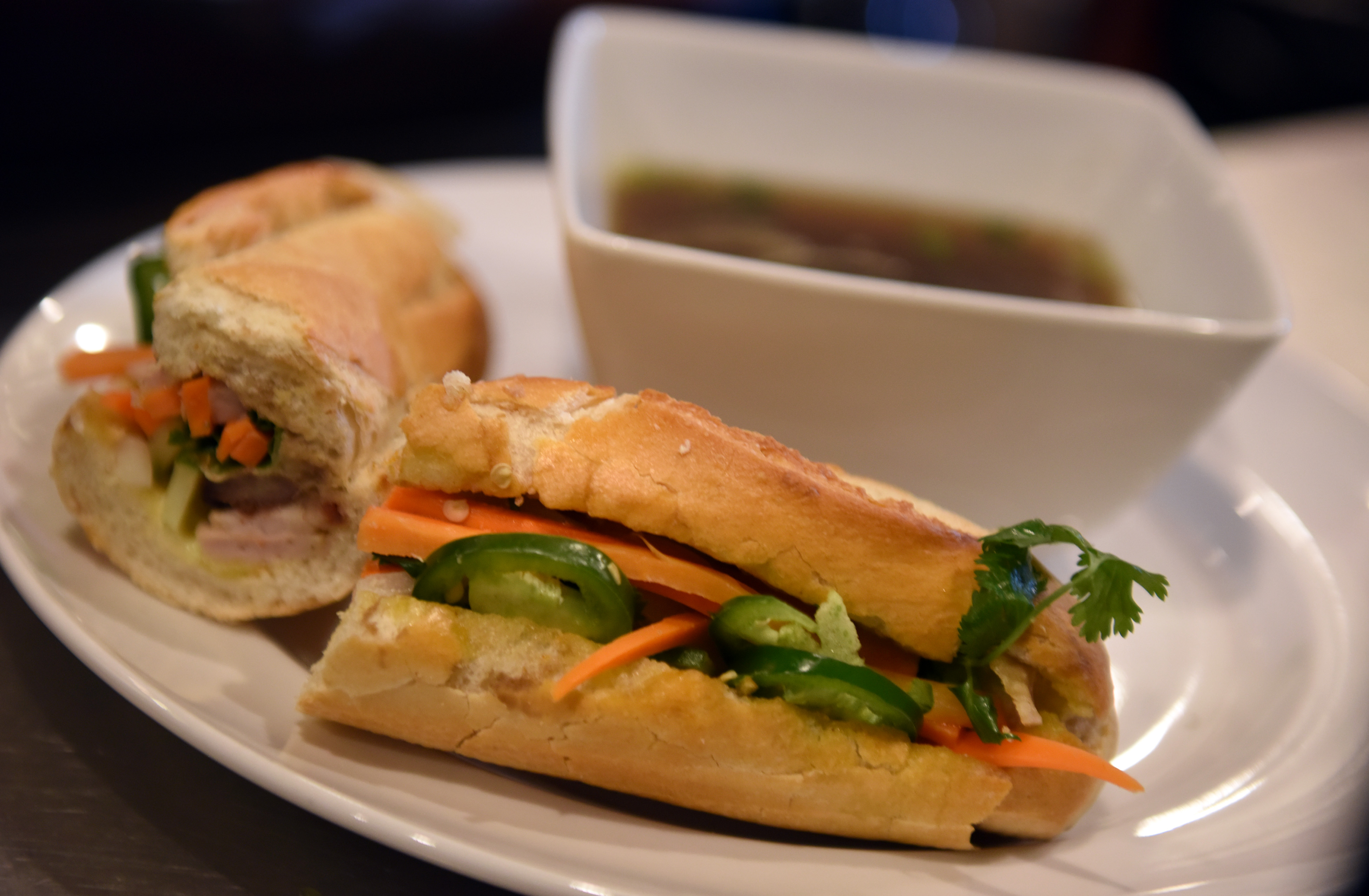 20170213smCookOff002-1 Executive chef Hoa Le prepared banh mi sandwich with pork and bone pho broth during Monday's cook off.