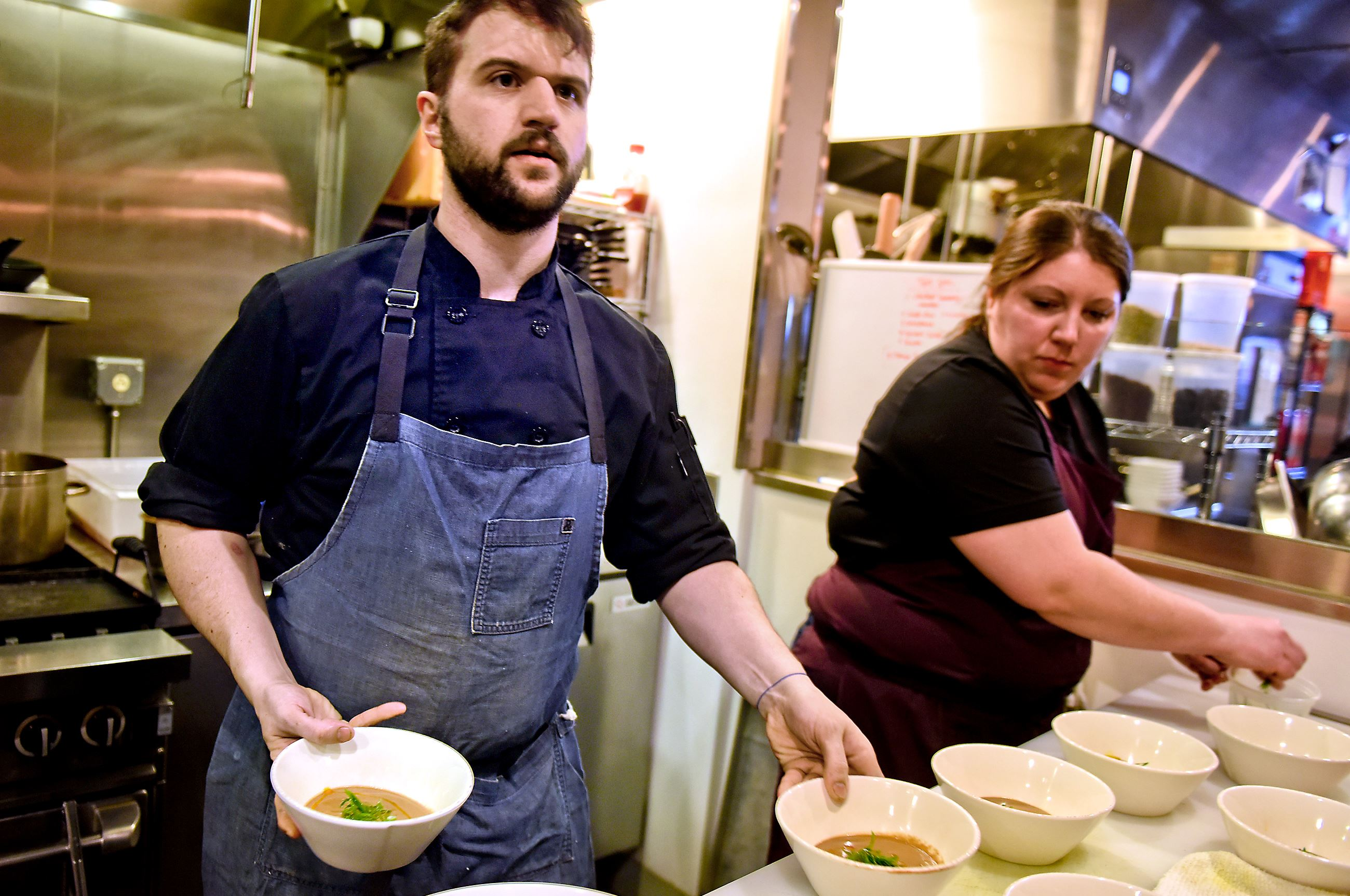 20170213smCookOff005-3 Chef Jesse Barlass, with help from Marisa Cantelli, makes final preparations during a cook off at Smallman Galley in the Strip District on Monday. Mr. Barlass was one of eight candidates auditioning for one of four openings at the restaurant incubator.
