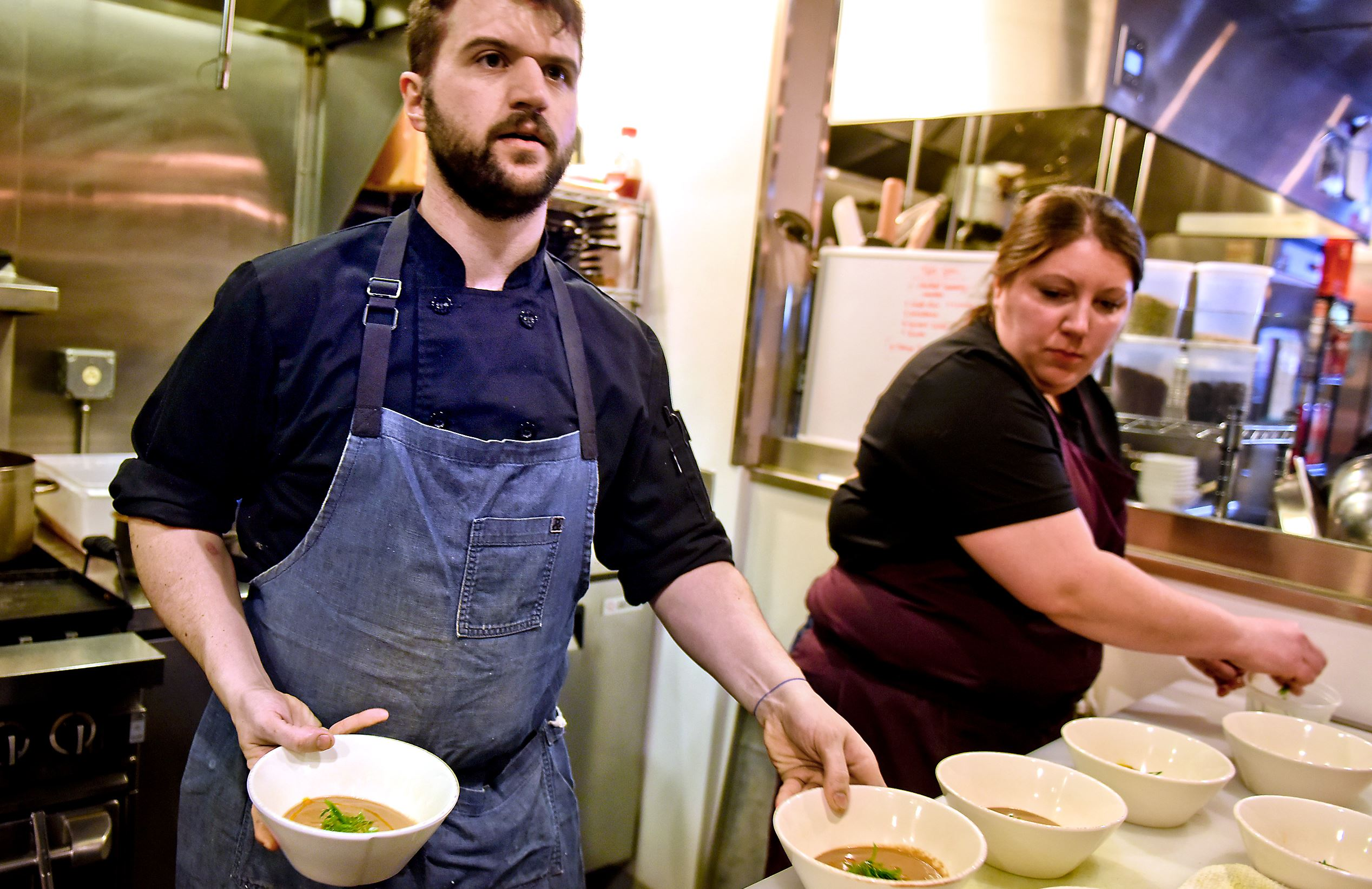 """20170213smCookOff005-3 Steve Mellon/Post-Gazette. Magazine Chef Jesse Barlass, with help from Marisa Cantelli, makes final preparations during a """"cook off"""" at Smallman Galley in the Strip District in March. Barlass was one of eight candidates auditioning for one of four openings at the restaurant incubator."""