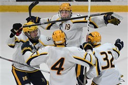 Central Catholic's Ryan Kingerski, center, celebrates after scoring the winning goal in double-overtime Wednesday at RMU Island Sports Center.