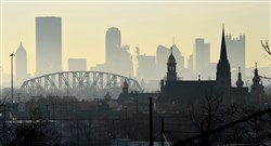 Steeples in the bottoms of McKees Rocks stand in the foreground of a hazy view of Pittsburgh's skyline.