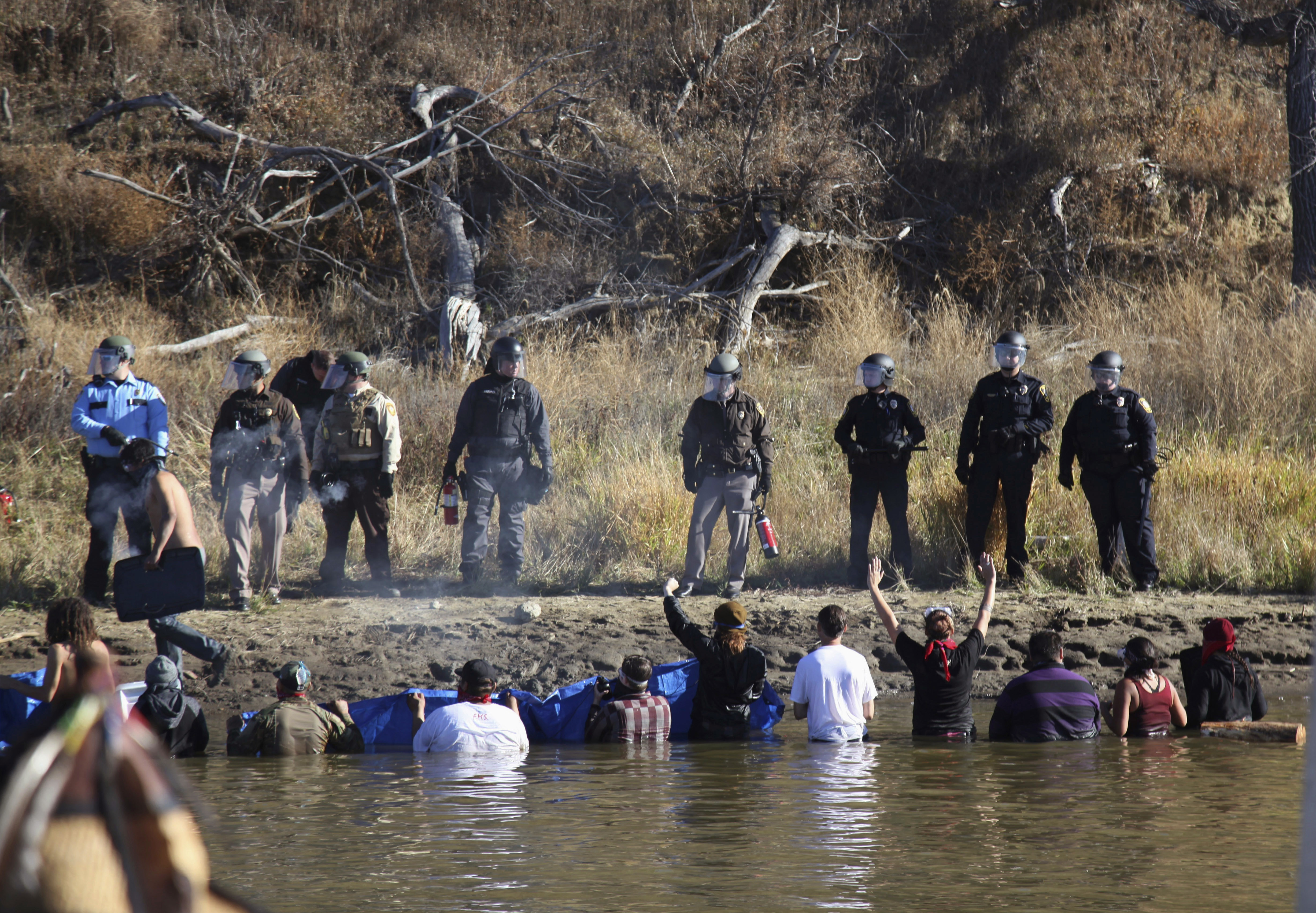 Oil Pipeline In this Nov. 2, 2016, file photo, protesters demonstrating against the expansion of the Dakota Access pipeline wade in cold creek waters confronting local police near Cannon Ball, N.D. North Dakota officials appear poised to go after the U.S. government — and thus U.S. taxpayers — to recoup more than $38 million in state expenses related to months of protests against the Dakota Access pipeline.