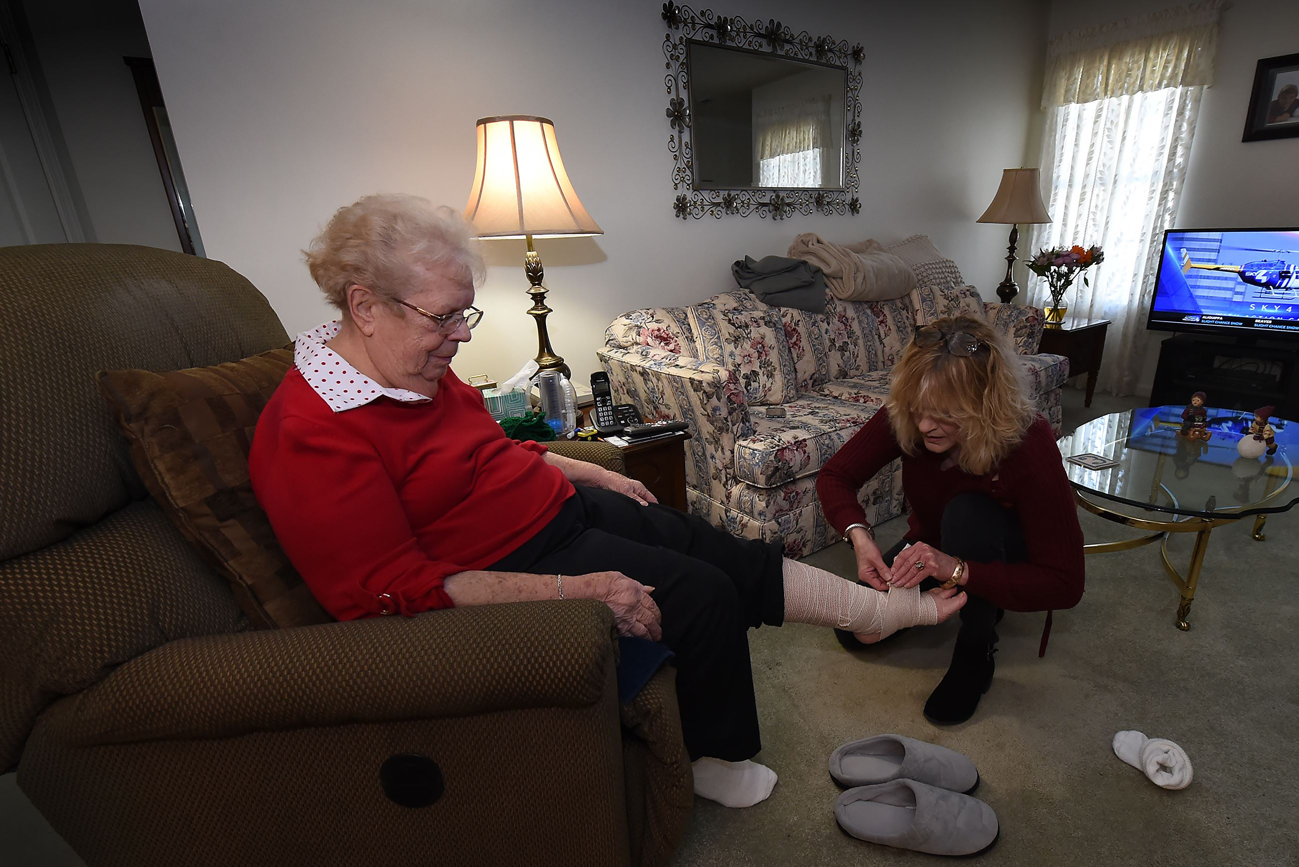 20170316pdHealthCare03-2 Cindy McDonald, an aide with Sunny Days In-Home Care, tightens a bandage on Betty Erdely's ankle in Ms. Erdely's Bethel Park home.