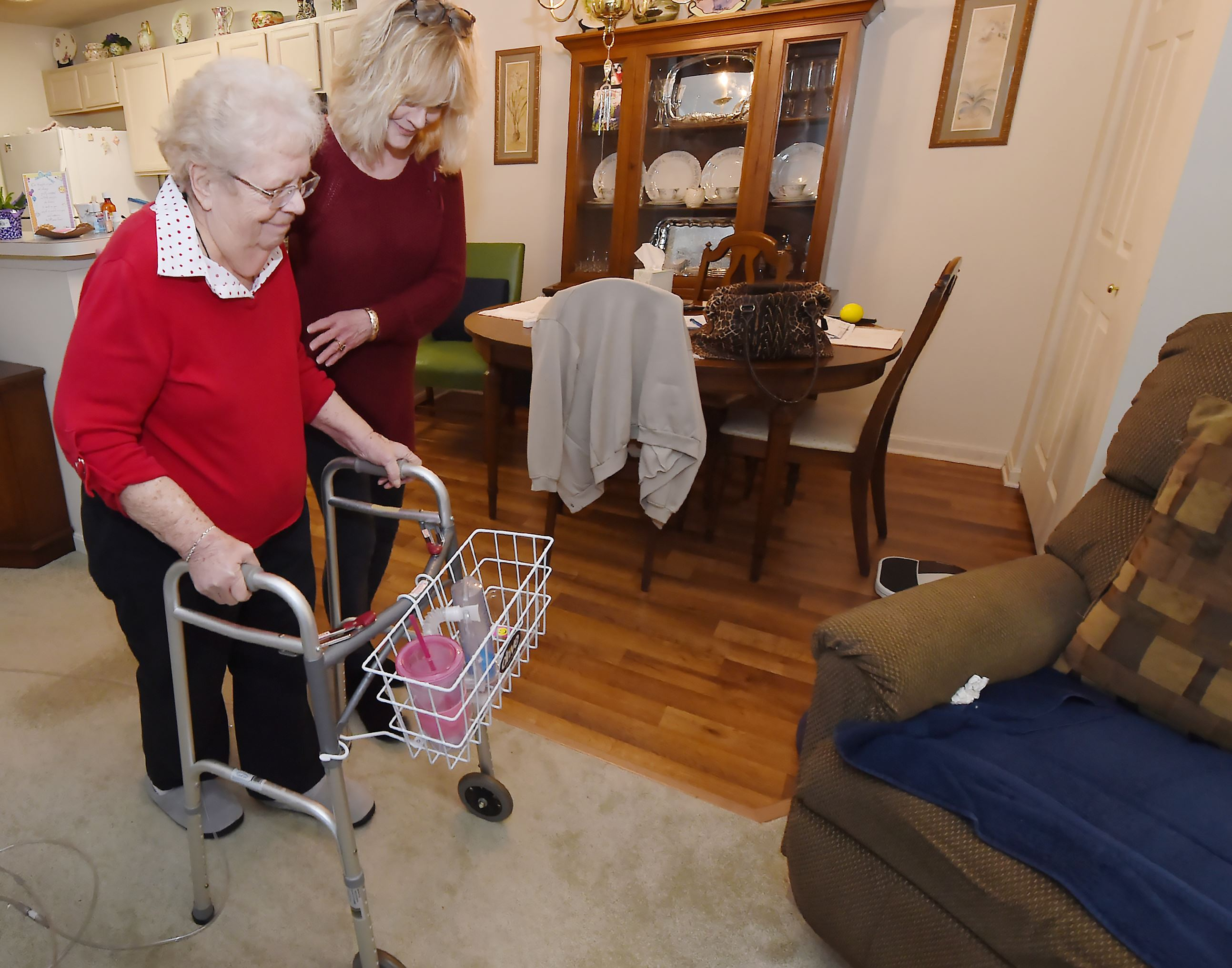 20170316pdHealthCare01 Cindy McDonald, an aide with Sunny Days In-Home Care, helps Betty Erdely to her chair in the living room of her Bethel Park home.