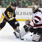 The Penguins' Patric Hornqvist tips pass between the legs of New Jersey Devils goalie Keith Kinkaid in the first period FRiday night at PPG Paint Arena.