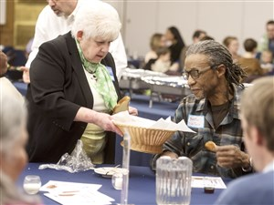 Arlene Smith from Temple Sinai passes bread to Wallace Hamilton from the Baptist Temple Church of Homewood at a dinner March 17 at Temple Sinai in Squirrel Hill.