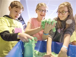From left, Matt Frye, Olivia Cramer, and Abby Buterbaugh play with slime at the Carnegie Science Center Slime Sleepover on March 17, 2017, at the North Shore.