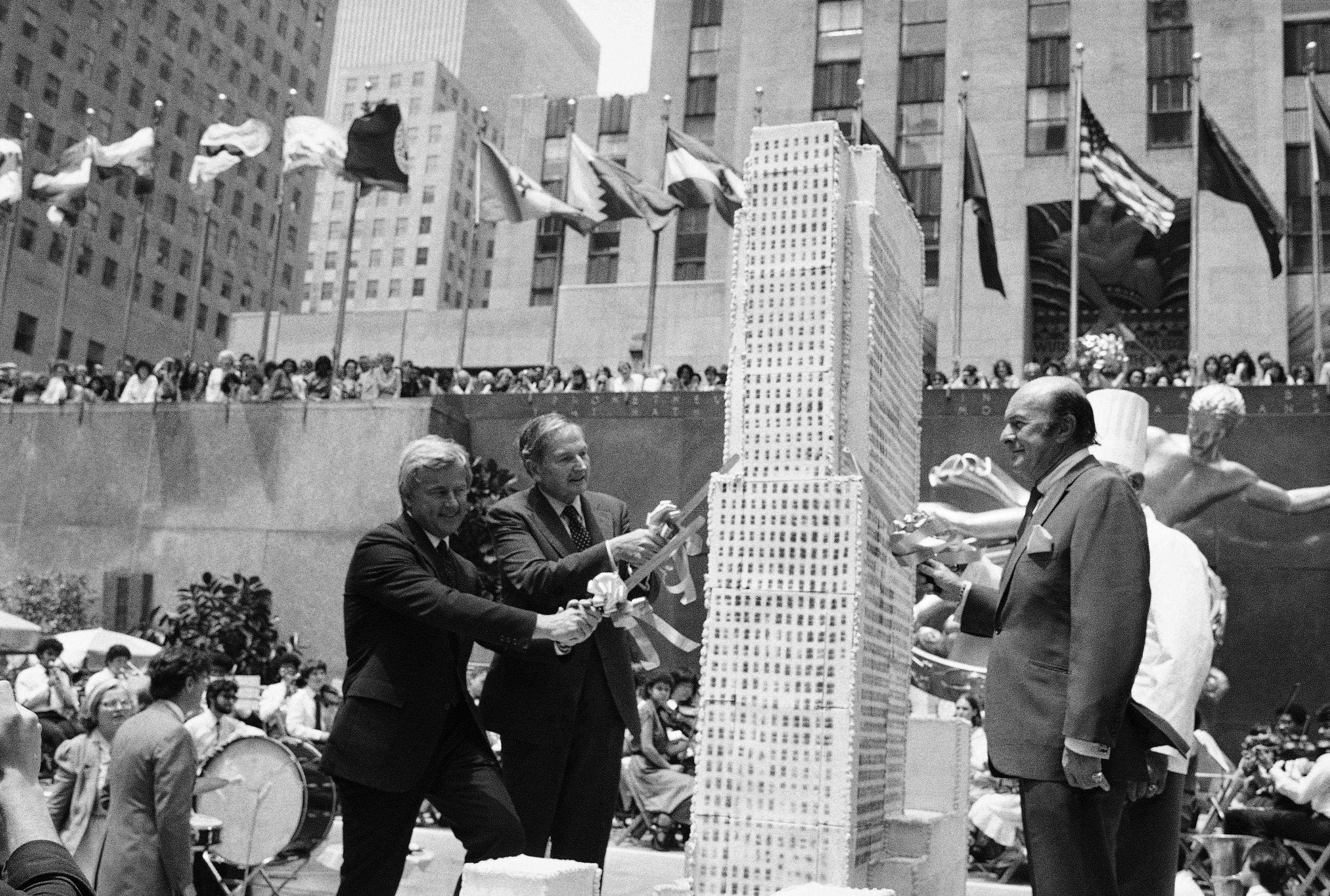 Obit David Rockefeller-3 FILE - In this June 16, 1982, file photo, David Rockefeller, second left, Rockefeller Center chairman and Center President Richard H. Voell, left, and New York City Board of Education President Joseph Barker, right, begin to slice up an eight-foot-tall culinary replica of Rockefeller Center in New York. The occasion marked the 50th birthday celebration of the midtown building complex. David Rockefeller, the billionaire philanthropist who was the last of his generation in the famously philanthropic Rockefeller family died, Monday, March 20, 2017, according to a family spokesman. (AP Photo/Ray Howard, File)
