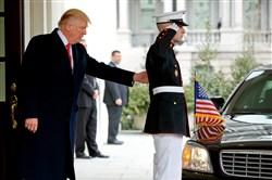 President Donald Trump moves a Marine out of the path of a vehicle carrying Iraqi Prime Minister Haider al-Abadi at the White House in Washington on Monday.