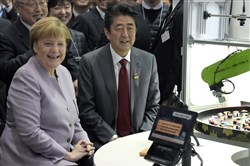 German Chancellor Angela Merkel, left, and the Prime Minister of Japan, Shinzo Abe, right, attend the presentation of a robot serving sushi during a walkabout at the IT trade fair CeBIT in Hanover, Germany, Monday.