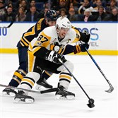 Sidney Crosby scores with one hand on a breakaway as Buffalo's Zach Bogosian tries to defend him during the first period Tuesday at the KeyBank Center in Buffalo, N.Y.