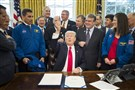 President Donald Trump hands out pens after signing the NASA transition authorization act Tuesday in the Oval Office of the White House. The bill boosts NASA's overall budget $19.5 billion, while refocusing efforts on deep space exploration and a manned mission to Mars.