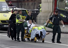 Emergency services transport an injured person to an ambulance, close to the Houses of Parliament in London, Wednesday, March 22, 2017.