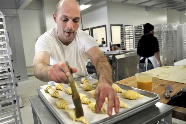 Fabian Moreau, owner of the French bakery La Gourmandine, works on a batch of croissants at the new location in Hazelwood on Tuesday.