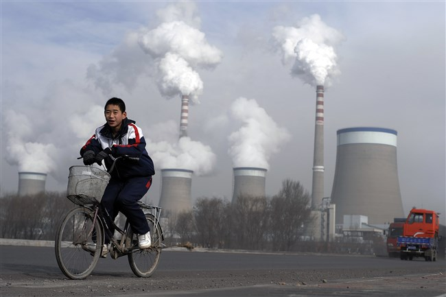 In this Dec. 3, 2009 photo, a Chinese boy cycles past cooling towers of a coal-fired power plant in Dadong, Shanxi province, China. Led by cutbacks in China and India, construction of new coal-fired power plants is falling worldwide, improving chances climate goals can be met despite earlier pessimism, three environmental groups said Wednesday, March 22, 2017.