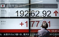 A woman looks at an electronic stock board showing Japan's Nikkei 225 index at a securities firm in Tokyo, Friday.