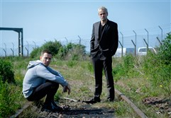 "Ewan McGregor as Mark Renton and Jonny Lee Miller as Simon on railway tracks in ""T2 Trainspotting."""